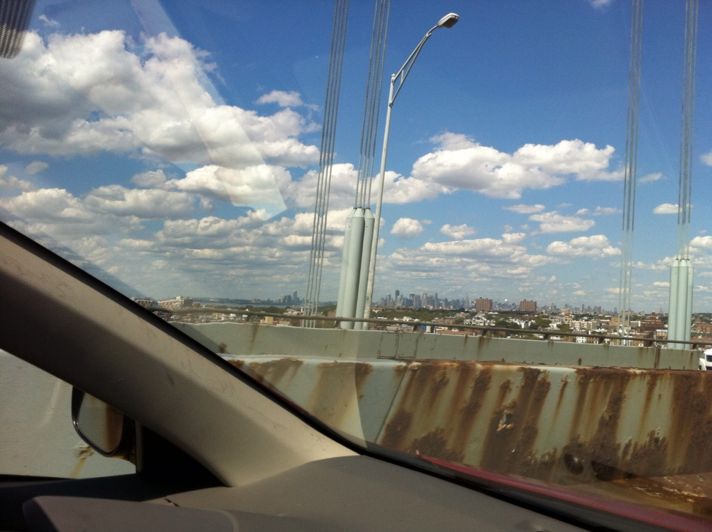Driving over a rusty bridge in New York City.